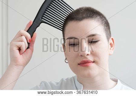 A Young Brunette Girl With Short Hair Is Combing Her Hair With A Huge Comb. Humor. Bald.
