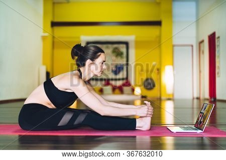 Young Woman Following Yoga Classes At A Distance On A Laptop. Concept Of Yoga Classes On The Interne