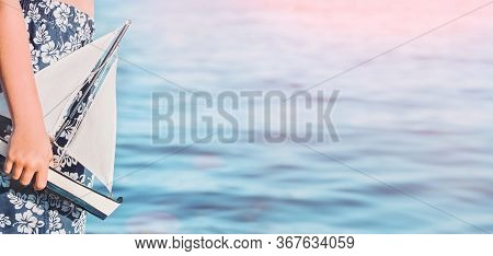 Child Caucasian Tanned Boy In Swimming Trunks At The Seaside Beach Holding Toy Sailing Boat. Blue Su