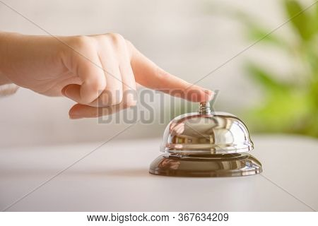 Hand Of Guest Ringing In Silver Bell. Reception Desk With Copy Space. Hotel Service. Selective Focus