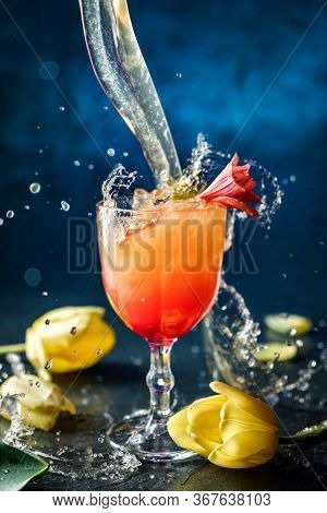 Fresh Tropical Cocktail With Ice And Flowers In Wineglass On Dark Blue Background. Studio Shot Of Dr