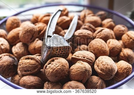Walnuts And Walnut Cracker. Many Of Whole Walnuts In A Nutshell. Selective Soft Focus. Natural Healt