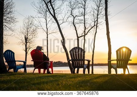 A Person Sitting In One Of Four Adirondack Chairs, Overlooking The Lake At Sunset On A Clear Day. Si