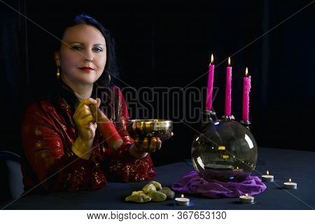 Young Clairvoyant And Fortuneteller With A Singing Bowl In Her Hands In A Magic Salon On A Black Bac