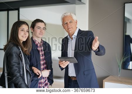 young couple visiting an apartment with a real estate agent