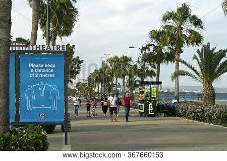 Limassol, Cyprus, May 22nd, 2020: Seafront Promenade Molos With A Social Distancing Sign Board And P