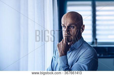 Worried Depressed Man Looking Throught The Window.