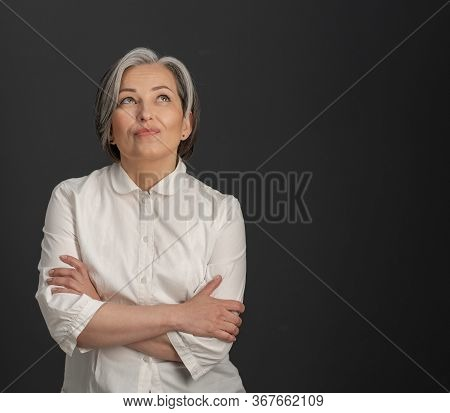 Creative Mature Woman Looking Upward Thoughtfully With Her Arms Crossed. Charming Silver-haired Woma