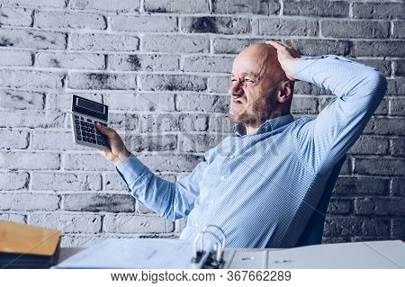 Finance Problems And Crisis. Worried Manager In The Office Counting Expences On Calculator.