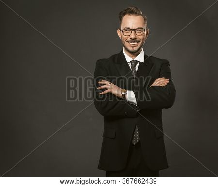 Successful Businessman. Well-dressed Businessman Toothy Smiles Standing With Arms Crossed On Dark Gr