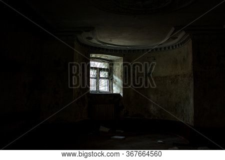 A Small Window In A Large Basement. White Light Penetrates The Dark Basement