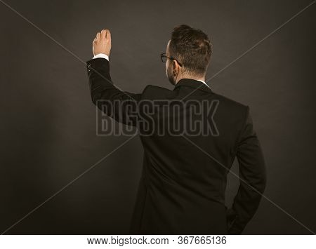 Smart Businessman Writes In Chalk On A Black Wall. Rear View Of White Collar Worker In Glasses Weari