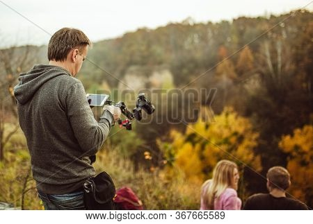 Young Man Going To Shoot Couple Of Tourists In Love Sitting On Top Of Mountain In Autumn Nature. Rea