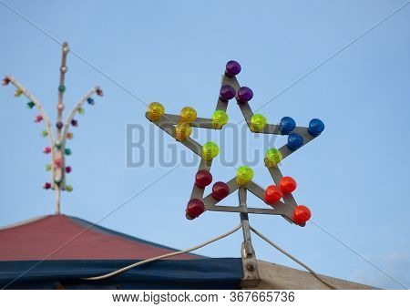Star-shaped Lamp With Multi-colored Light Bulbs. Star-shaped Illumination At The Top Of The Carousel
