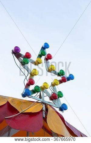 Lamp With Multi-colored Light Bulbs. Star-shaped Illumination At The Top Of The Carousel. Illuminati