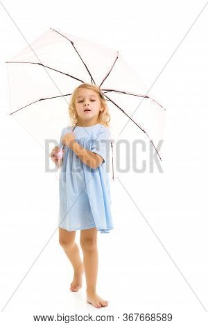 A Beautiful Little Girl Hid Under An Umbrella. The Concept Of Summer Vacation, Style And Fashion. Is