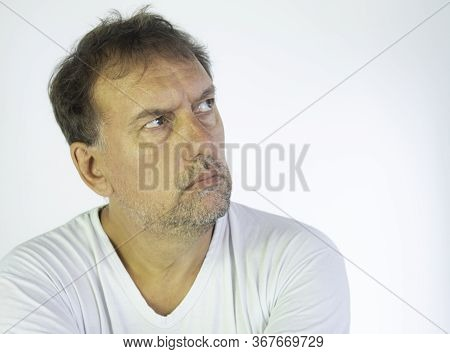 Middle-aged Man With White T-shirt And Quarantined Boredom. Altered Concentration And Tiredness At H