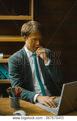 Businessman Works With Computer In Office. Thoughtful Caucasian Man Looks Into A Computer Monitor To