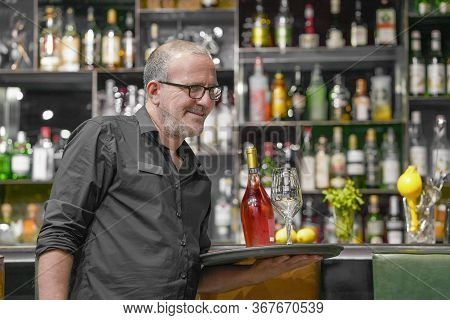 The Bartender Serves A Table. Bartender Carries A Wine Glasses And Bottle Wine On A Tray In Hotel Re