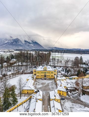 Aerial View Of Schloss Hellbrunn Covered In Snow With View Of Untersberg Near Salzburg Outskirts In