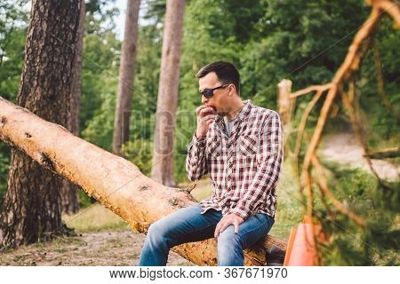 Portrait Young Male Hiker Eating Apple. Tourist At Forest, Stop For Rest And Eat Apple. Fit Man Eati