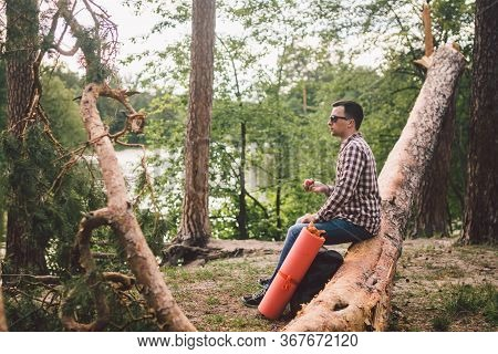 Man Eating An Apple On Hiking Trip In Forest. Hiker Taking Break While Trekking In Wilderness. Male