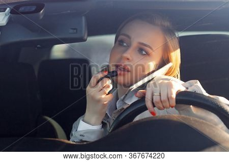 Woman New Driver Sitting In Car, Doing Make Up, Using Lipstick, Talking On Phone. Careless And Dange