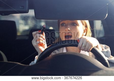 Woman New Driver Sitting In Car, Doing Make Up, Using Lipstick, Careless And Dangerous Driving. No C