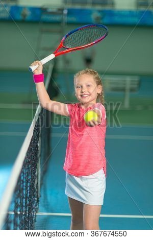 A Girl Plays Tennis On An Indoor Tennis Court.