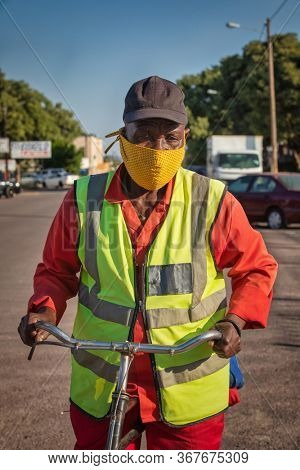 African man with a mask  dressed with a reflective vest riding a bicycle in town .