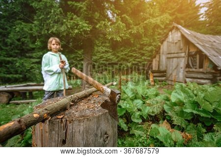 Young Teenager Boy Standing Near Axe In Carpathian Village, Supervision For Kids Concept