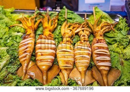 Grilled Squid, Street Food. Stuffed Squid. Salat