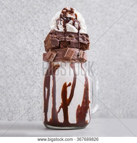 Milkshake With Whipped Cream, Brownie, Chocolate Bar And Chocolate Sauce On A Grey Surface