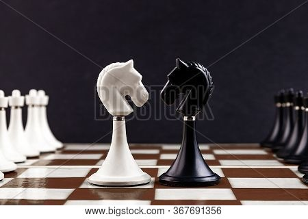 White And Black Chess Pieces On A Chessboard On A Dark Background. Business Concept. Game, Strategy,