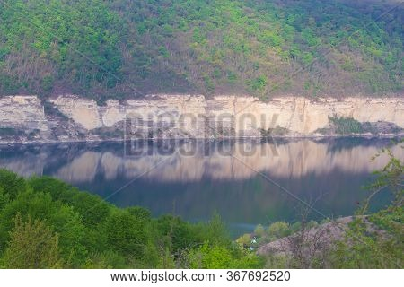 Landscape With Mountains, Forest And A River In Front. Beautiful Scenery