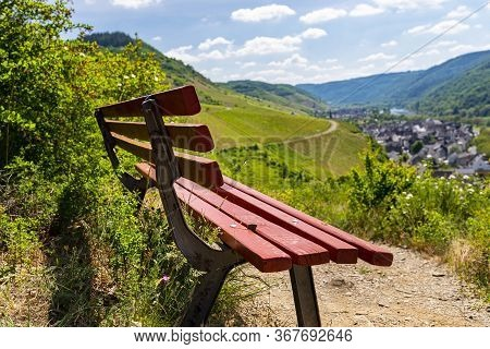 A Red Bench Standing On The Hill Of The Winery, In The Background Beautiful Wineries In The Spring.