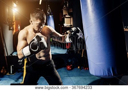 A Concentrated Professional Boxer Hits A Punching Bag.