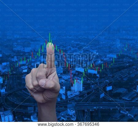 Hand Pressing To Trading Graph Of Stock Market Over Modern City Tower, Street, Expressway And Skyscr