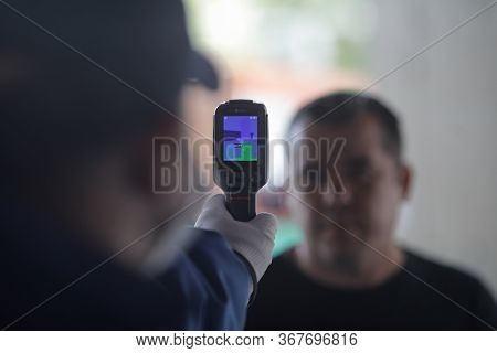 Bucharest, Romania - May 7, 2020: Details With A Shop Security Guard Termoscanning Customers Before