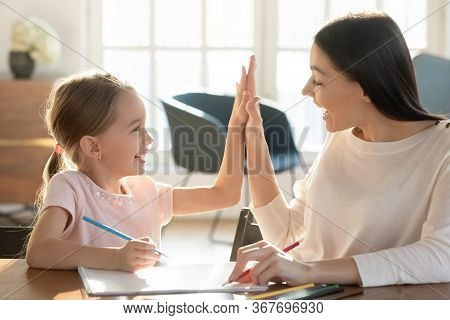 Overjoyed Mom And Little Daughter Give High Five Studying
