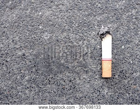 Single Cigarette Stub On Dark Concrete And Small Black Gravel Stone Road With Copy Space, Dirty Garb