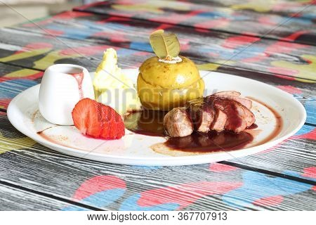 Peking Duck On A White Plate With Mashed Potatoes And Pomegranate Sauce