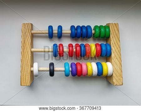 Colored Children's Abacus Made Of Wood On A White Gradient Background. Educational Games For Childre