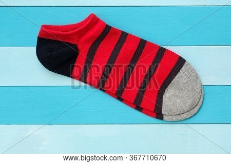 Red Cotton Striped Socks Top View. Short Bright Socks On A Wooden Blue Background. A Pair Of Socks F
