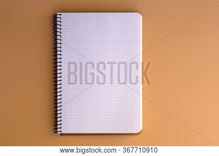 Notebook With Spring And Sheets In A Cage Top View. Blank Paper In A Notebook On A Beige Background.