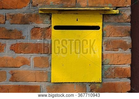 Old Metal Yellow Personal Mailbox In A Red Brick Wall. Box For Receiving Letters And Other Paper Mai