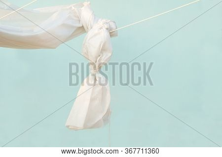 Tied End Of Fabric Canopy Hanging On Ropes. White Awning Hanged On A Wall Of Azure Color.