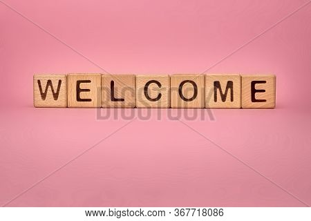Welcome Word Made With Building Blocks, Business Concept. Word Welcome On Pink Background. Global Ma