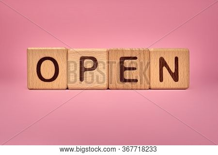Open Word On Wooden Cubes. Open Word Welcoming Clients, Visitors, Guests. Pink Background With Text