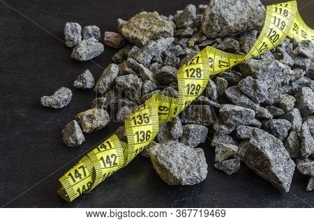 A Tailor Meter Lies On A Pile Of Rubble. Yellow Ribbon Of Swirling Tailor Meter Among Granite Rubble